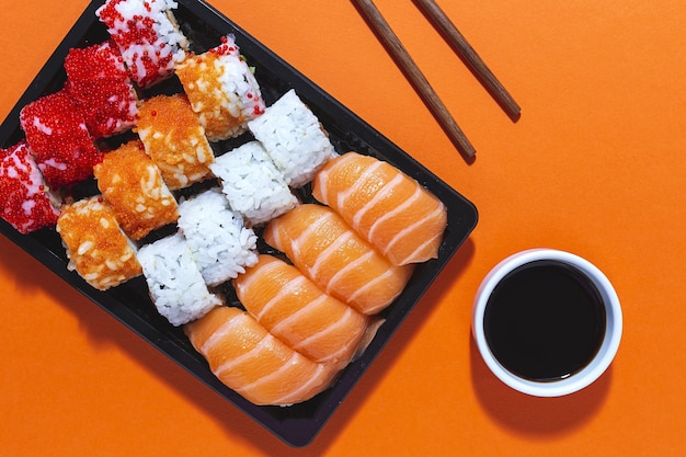 Japanisches lebensmittelkonzept. verschiedene sushi zum mitnehmen in der schachtel. zum mitnehmen. lieferung. meeresfrüchte
