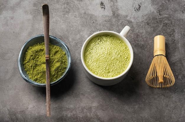 Japanisches matcha-grüntee-pulver, bambuslöffel und schneebesen,