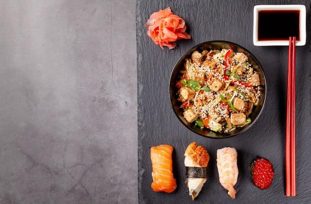 Japanisches mittagessen mit nudeln, sushi mit garnelen, rotem kaviar, aal, thunfisch.