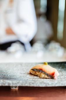 Japanisches omakase-essen shima aji sushi mit frischem wasabi, serviert von hand auf einem schwarzen steinplatte.