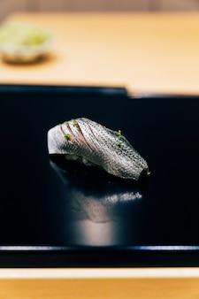 Japanisches omakase-menü: saba sushi (makrele) mit gehackter yuzu-schale auf glänzendem schwarzblech bestreuen. japanische luxusmahlzeit.