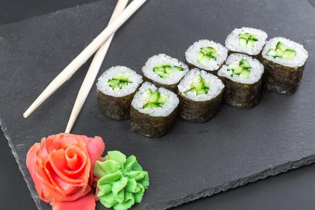 Japanisches restaurant, sushirolle auf schwarzer schieferplatte.