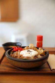 Japanisches rindfleisch des japanischen lebensmittels gyudon auf der reisschüssel überstiegen mit ei auf holztisch