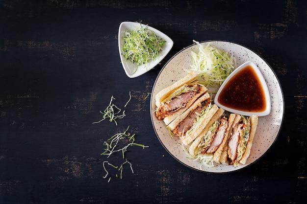 Japanisches sandwich mit paniertem schweinekotelett, kohl und tonkatsu-sauce.