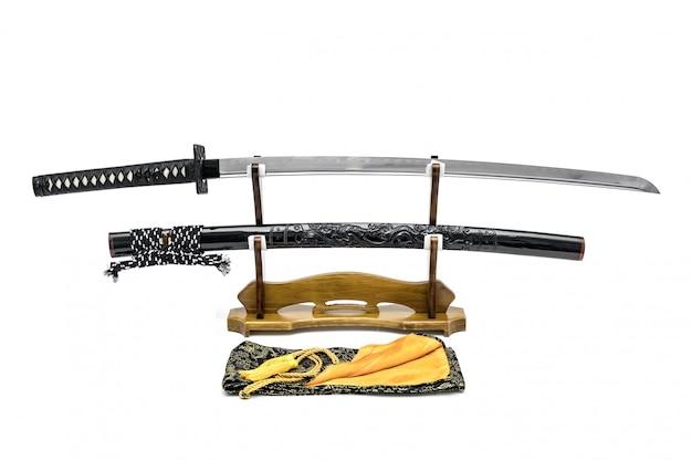 Japanisches schwert mit glänzender schwarzer drachenscheide auf holzständer und seidentasche in der front