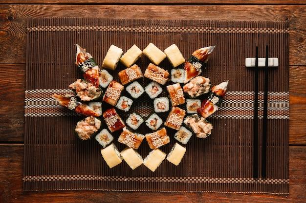 Japanisches sortiertes leckeres frisches sushi-set, serviert auf brauner strohmatte, flach. essenskunst, mosaik aus köstlichen bunten brötchen. menüfoto des luxusrestaurants.