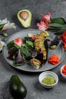 Japanisches sushi - grüner drache. avocado-, zwiebel-, lachs- und sushi-käse