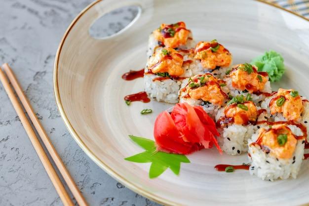 Japanisches sushi mit sesam und sahneglasur auf grauem hintergrund