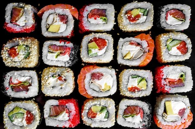 Japanisches sushi rollt auf schwarzem hintergrund, draufsicht.