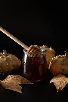 Jar honig mit getrockneten blättern und kürbis auf der seite lokalisiert auf einem dunklen hintergrund