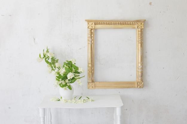 Jasmin in vase und altem holzrahmen im vintage weißen interieur