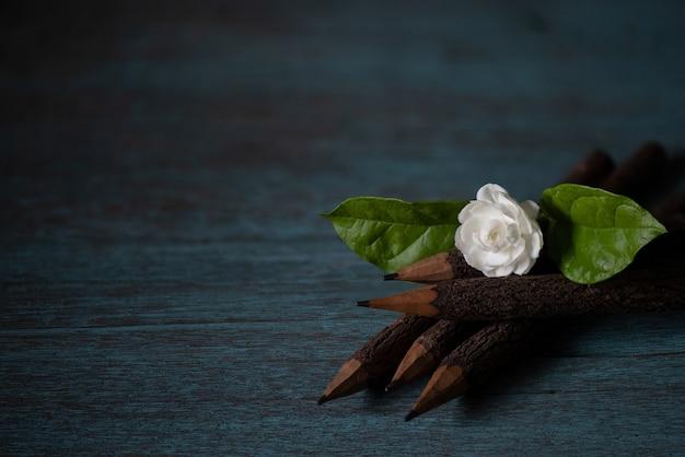 Jasminblüte und bleistifte auf einer alten holzoberfläche.
