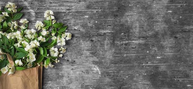 Jasminblüten-blumenzweig auf hölzernem hintergrund mit platz für text. bannerformat