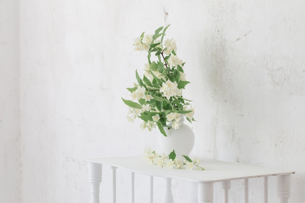 Jasminblüten in der vase auf der alten wand des hintergrunds