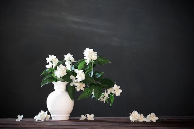 Jasminblüten in keramikvase auf weißem hintergrund