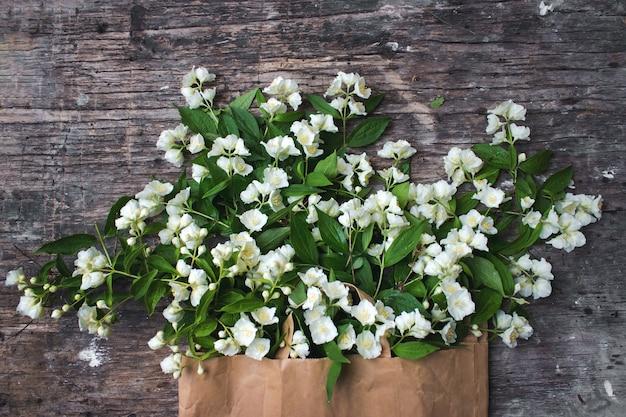Jasminblüten und -blätter auf braunem holzbrett. flache lage, ansicht von oben, kopienraum.