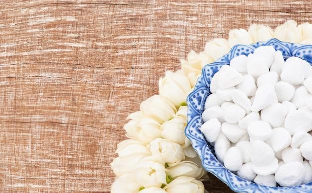 Jasmingirlande und bunte blume in wasserschalen, die wasser, parfüm, marmorierten kalkstein, pfeifenpistole verzieren und duften, isoliert auf einem alten holz für songkran-festival oder thailändisches neues jahr.