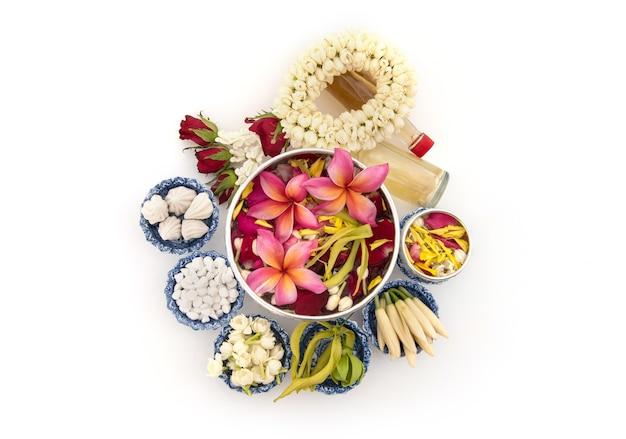 Jasmingirlande und bunte blume in wasserschalen, die wasser, parfüm, marmorierten kalkstein, pfeifenpistole verzieren und duften, isoliert für songkran-festival oder thailändisches neues jahr.