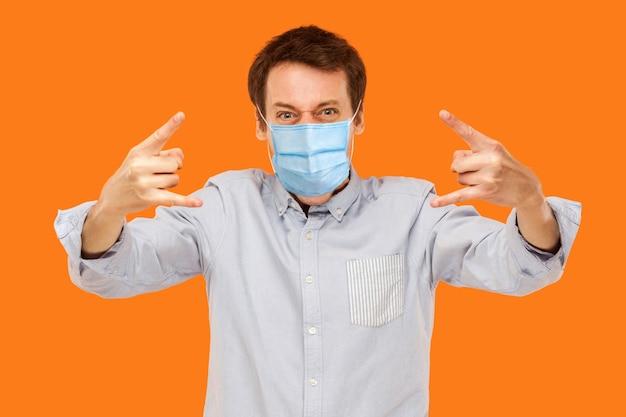 Jawohl. porträt eines jungen arbeiters mit chirurgischer medizinischer maske, der mit felshörnern und loolong an der schreienden kamera steht. indoor-studioaufnahme auf orangem hintergrund isoliert.