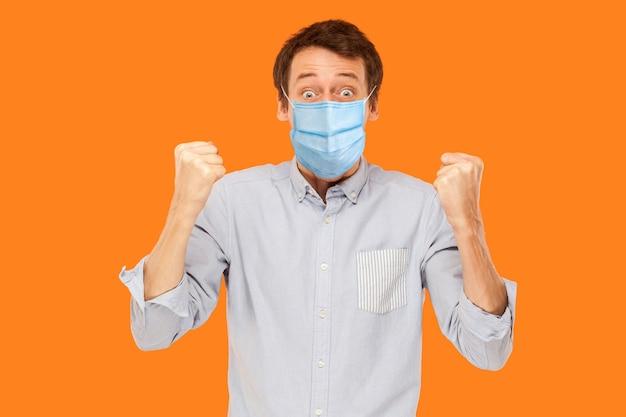 Jawohl. porträt eines überraschten jungen arbeitermannes mit chirurgischer medizinischer maske, der seinen sieg steht und feiert und in die kamera schaut. indoor-studioaufnahme auf orangem hintergrund isoliert.