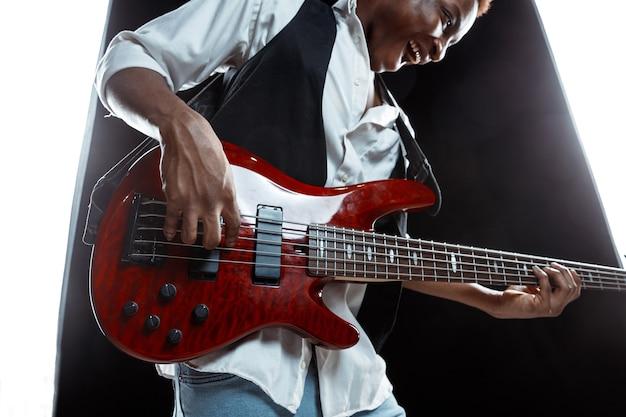 Jazzmusiker, der bassgitarre im studio an einer schwarzen wand spielt