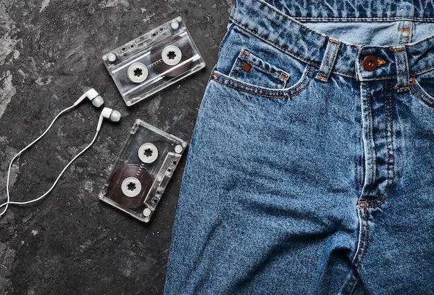 Jeans, audiokassette, kopfhöreranordnung auf einem schwarzen betontisch. konzeptionelles foto, das die faszination des musikhörens veranschaulicht. draufsicht.