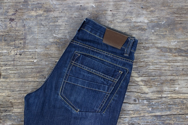 Jeans auf holzhintergrund, flach. moderne kleidung.