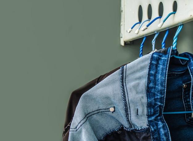 Jeans, die am aufhänger am sonnigen tag sich waschen und hängen