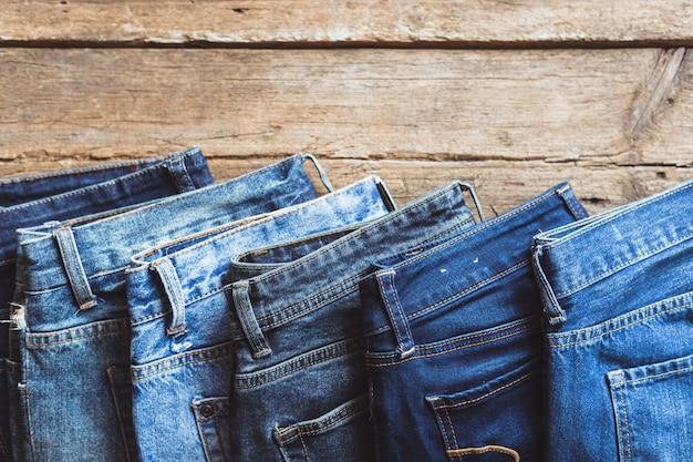 Jeans gestapelt auf einem hölzernen hintergrund