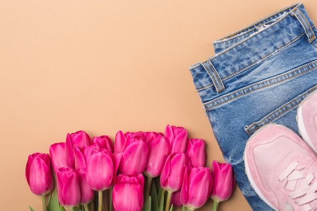 Jeans, turnschuhe und rosa tulpen. flach legen mode frühling konzept