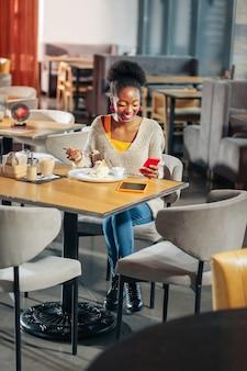 Jeans und pullover dunkelhaarige frau mit jeans und hellem pullover, die in der cafeteria sitzt und süßen kuchen isst