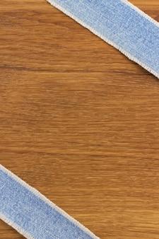 Jeansstreifen am hölzernen texturhintergrund