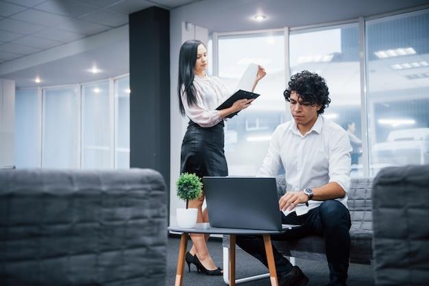 Jeder ist konzentriert. freiberufliche tätigkeit im büro mit fenstern dahinter. zwei personen sind berufstätig. kerl, der silbernen laptop verwendet. mädchen las dokument
