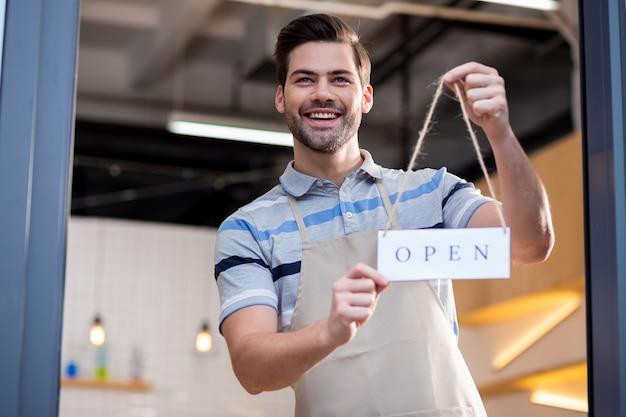 Jeder ist willkommen. erfreuter netter positiver mann, der ein etikett hält und lächelt, während er kunden einlädt