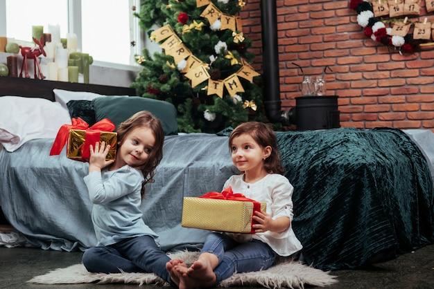 Jeder von ihnen hat ein gutes geschenk. weihnachtsferien mit geschenken für diese beiden kinder, die drinnen im schönen raum neben dem bett sitzen