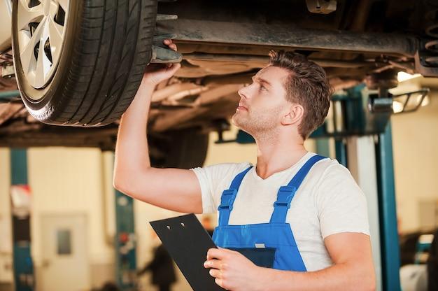 Jedes detail prüfen. selbstbewusster junger mann in uniform, der eine lampe hält, während er in der werkstatt unter einem auto steht