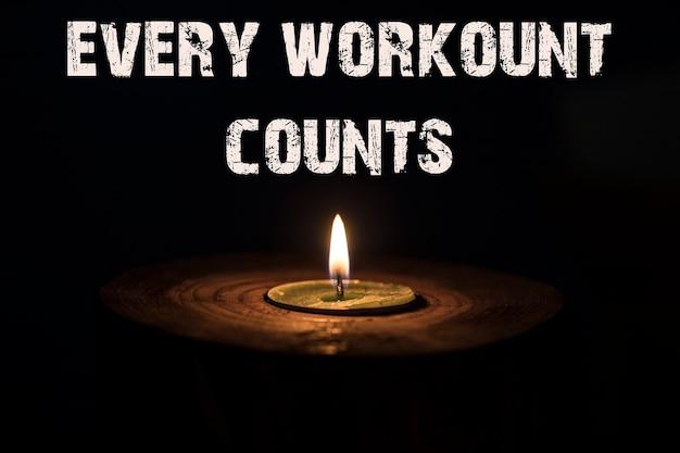Jedes workout zählt - weiße kerze mit dunklem hintergrund - im kerzenständer aus holz.