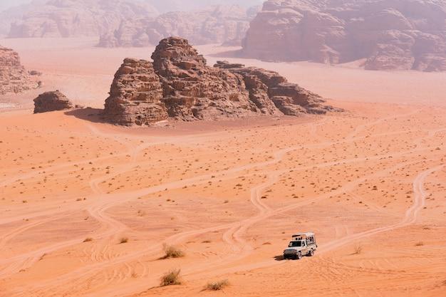 Jeep-safari in der wüste wadi rum, jordanien. touristen im auto fahren im gelände zwischen den felsen im sand