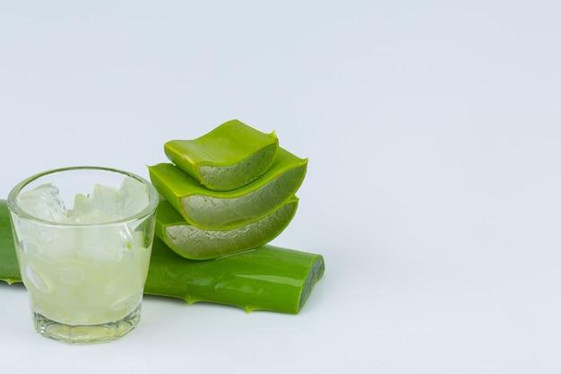 Jel von aloe vera in einem glas mit aloe vera blatt ist fast zusammen auf weißer wand.