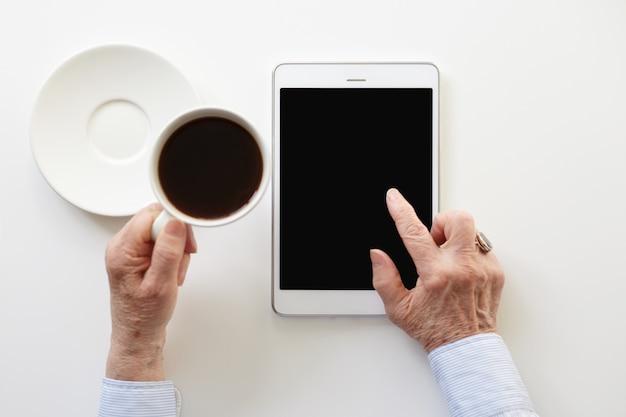 Jemand benutzt das touchpad, während er eine tasse kaffee trinkt