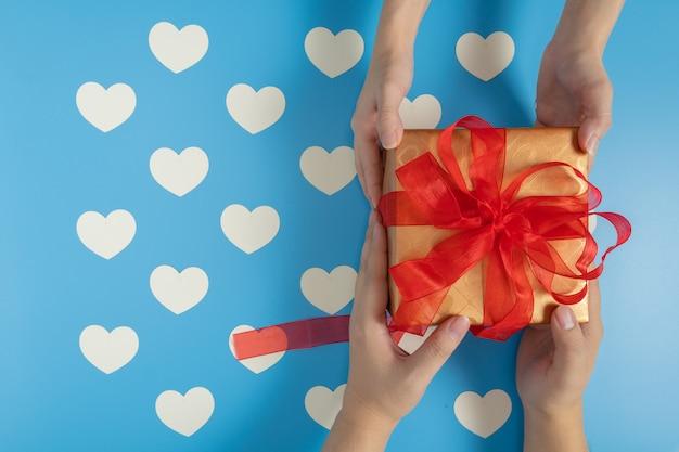 Jemand, der eine geschenkbox sendet, die mit rotem band auf blauem hintergrund mit weißem herzmuster gebunden ist