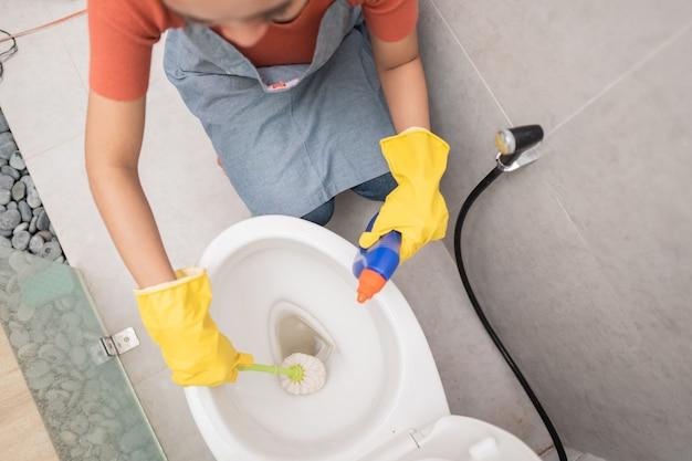 Jemand, der handschuhe trägt, reinigt die toilette mit einer bürste und einem porzellanreiniger im badezimmer