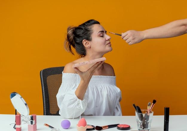 Jemand, der lidschatten mit make-up-pinsel auf augen des schönen mädchens anwendet, das am tisch mit make-up-werkzeugen sitzt, die lidschatten-palette lokalisiert auf orange wand halten