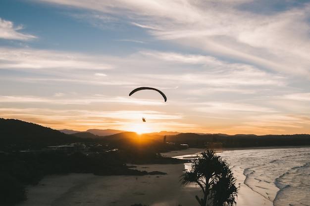 Jemand gleitschirmfliegen bei sonnenuntergang am strand erstaunliche landschaft