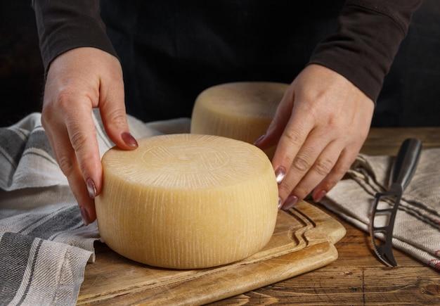 Jemand hände legen ein rad frischen hausgemachten käses auf ein holzbrett aus nächster nähe