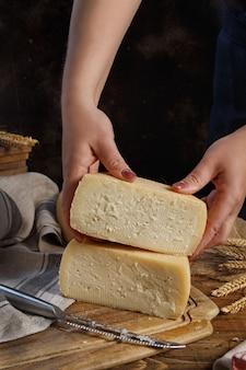 Jemand hände legen stücke frischen hausgemachten käses auf ein holzbrett aus nächster nähe