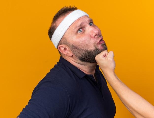 Jemand schlägt in das kinn eines erwachsenen slawischen sportlichen mannes mit stirnband und armbändern, isoliert auf oranger wand mit kopierraum
