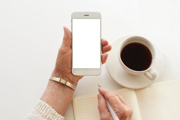 Jemand telefoniert, während er eine tasse kaffee trinkt