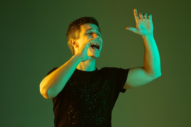 Jemanden anrufen, schreien. porträt des kaukasischen mannes lokalisiert auf grünem studiohintergrund im neonlicht. schönes männliches modell im schwarzen hemd. konzept der menschlichen emotionen, gesichtsausdruck, verkauf, anzeige.
