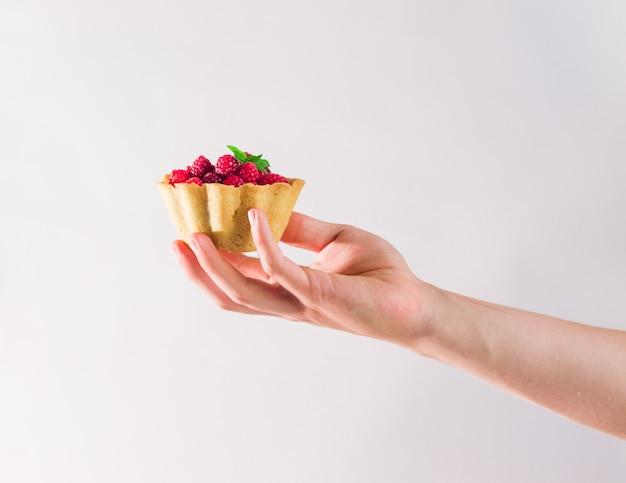 Jemandes hand hält hausgemachtes himbeergebäck. sommerbeeren-minitörtchen mit vanillepudding und minzblättern. frische desserts auf dem weißen hintergrund lokalisiert. freier kopierplatz.